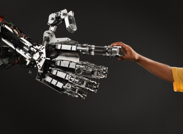 Robot and boy shaking hands --- Image by © Mike Powell/Corbis