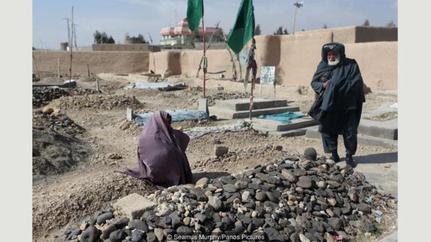 Rahila Muska'nın anne babası mezarının yanında görülüyor. Kızlarının şiir yazdığını reddettiler. (kaynak: Simıs Morfi/Panos Fotoğrafçılık])